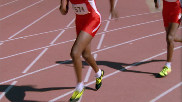medium shot two black male runners passing baton in track relay race - lycra stock-videos und b-roll-filmmaterial