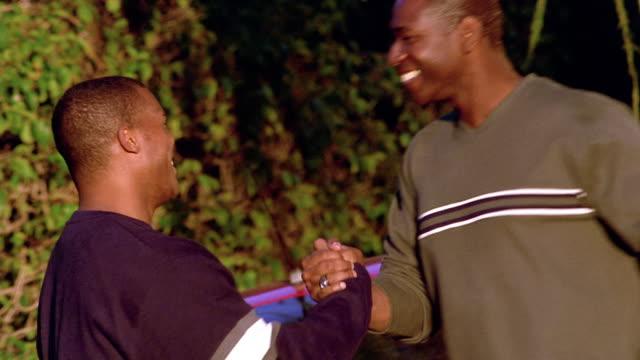 stockvideo's en b-roll-footage met medium shot two black men shaking hands and hugging outdoors / arizona - men