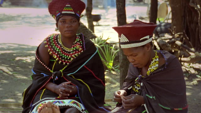 medium shot two black zulu women in native dress sitting outdoors / durban, kwazulu-natal, s. africa - 民族衣装点の映像素材/bロール