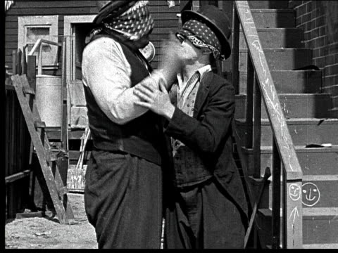 1918 b/w medium shot two blindfolded men kiss each other, remove blindfolds, then begin to fight - moustache stock videos & royalty-free footage