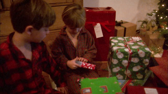 Medium shot two boys opening Christmas presents in living room / boy opening video game and cheering
