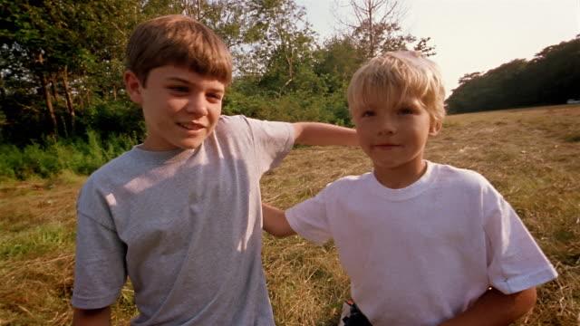vídeos de stock, filmes e b-roll de medium shot two boys putting arms around each other and smiling - de braços dados