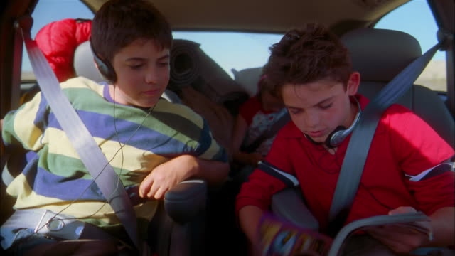 Medium shot two boys sitting in backseat of minivan and looking at magazine