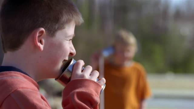Medium shot two boys talking on tin can telephone/ Goram, Maine
