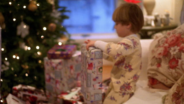 Medium shot two boys wearing pajamas open gifts with Christmas tree in background