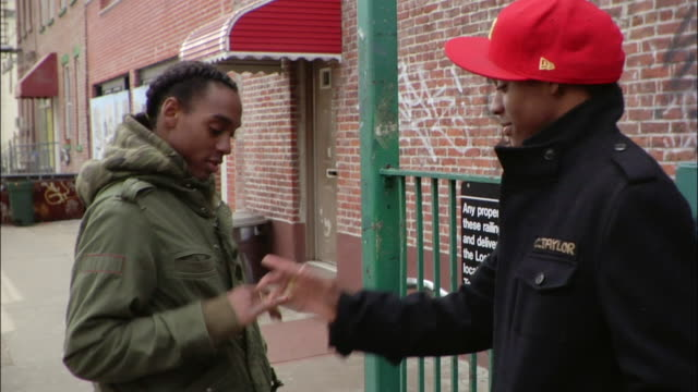medium shot two brothers giving each other street handshakes near subway sign / new york city, new york, usa - brother stock videos & royalty-free footage