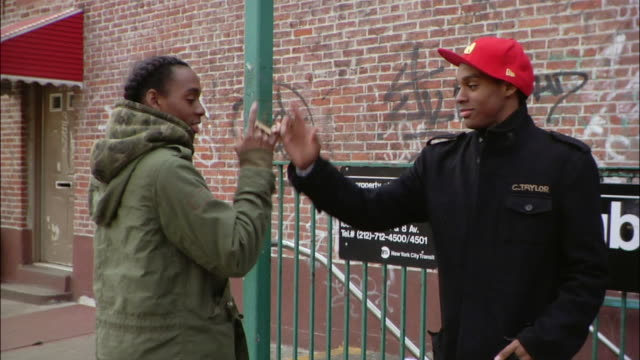 stockvideo's en b-roll-footage met medium shot two brothers giving each other street handshakes near subway sign / new york city, new york, usa - iemand een hand geven