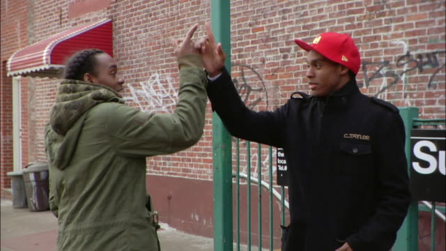 medium shot two brothers giving each other street handshakes near subway sign / new york city, new york, usa - 2007 stock videos & royalty-free footage