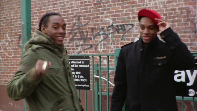 vidéos et rushes de medium shot two brothers showing off their knuckle rings near subway sign / new york city, new york, usa - casquette de baseball