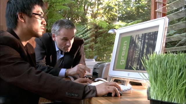 medium shot two businessmen using computer and talking in office - ansvarsfullt företagande bildbanksvideor och videomaterial från bakom kulisserna