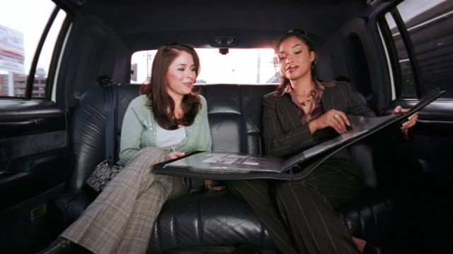 Medium shot two businesswomen looking at portfolio in limo / smiling and laughing / one woman taking cell phone call