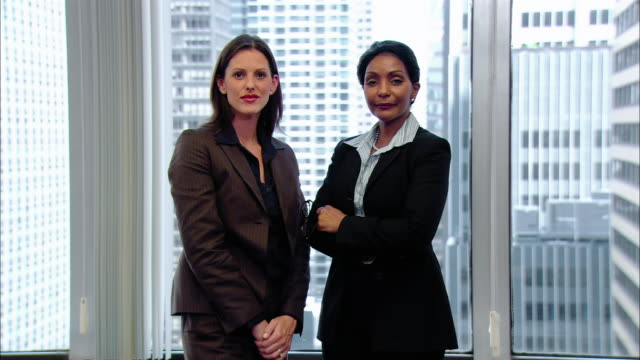 medium shot two businesswomen standing side-by-side in front of window/ women high-fiving each other/ new york, new york - side by side stock videos & royalty-free footage