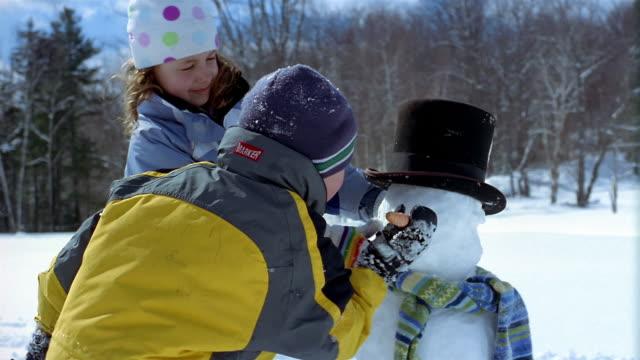 medium shot two children building snowman / boy sticking carrot onto face of snowman / vermont - schneemann stock-videos und b-roll-filmmaterial