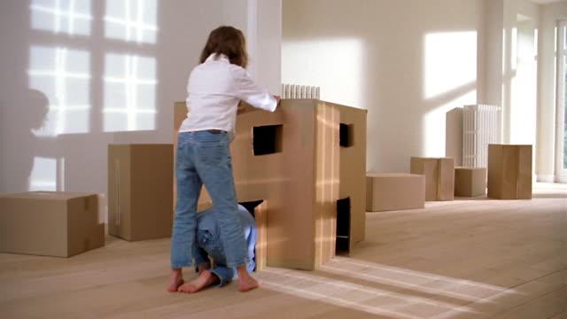 medium shot two children crawling into door of cardboard box house w/cut out windows on floor of living room - verstecken stock-videos und b-roll-filmmaterial