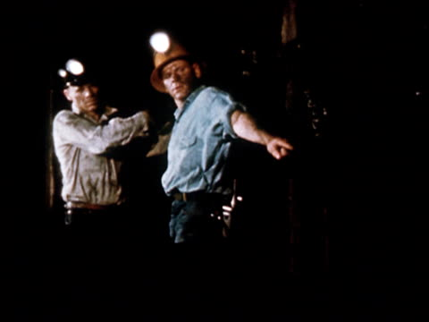 vidéos et rushes de 1949 medium shot two coal miners with lighted helmets in mine/ miner turning and pointing something out to other miner/ audio - 1949