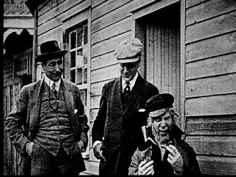 1914 b/w medium shot two con men giving cigar to elderly sailor smoking a pipe  - 1914 stock videos & royalty-free footage