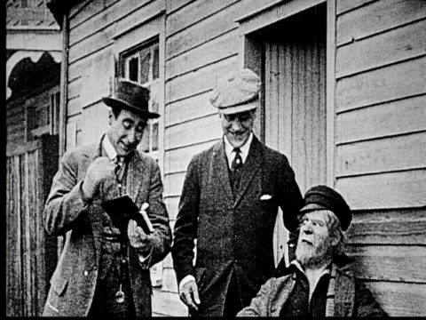 1914 b/w medium shot two con men with wallet full of money talking to elderly sailor and walking away together  - 1914 stock videos & royalty-free footage