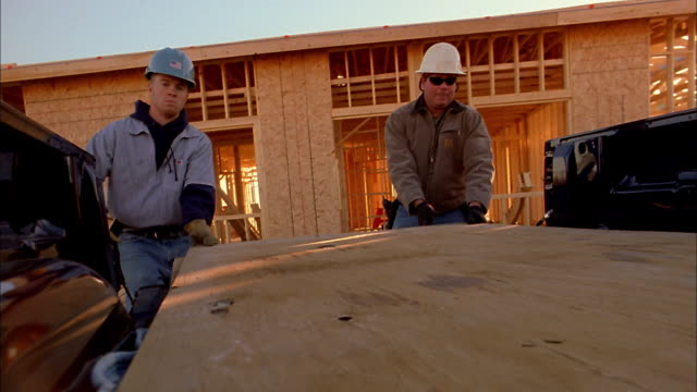 medium shot two construction workers unloading wood panels from truck / phoenix, arizona - entladen stock-videos und b-roll-filmmaterial