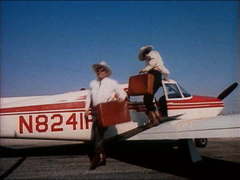 stockvideo's en b-roll-footage met medium shot two cowboys getting out of prop plane with suitcases / pan walking past sign towards world's fair - cowboyhoed