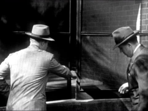 1947 Medium shot two detectives doing forensics work, measuring part of open window/ Dearborn, Michigan