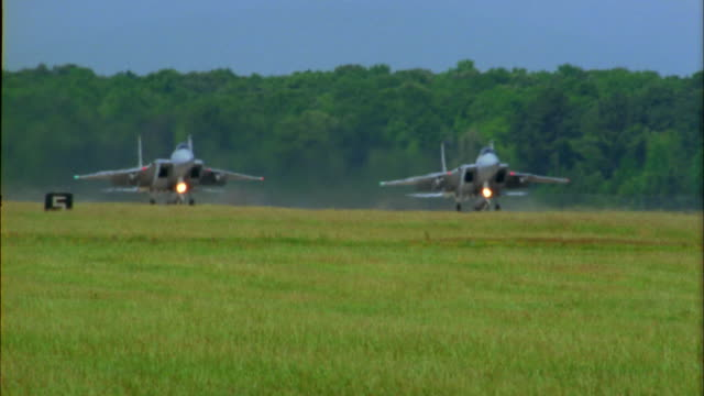 Medium shot two F-15 fighter jets taking off and raising landing gear