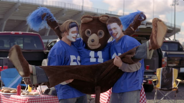 medium shot two face-painted football fans lifting up bear mascot at tailgate party/ connecticut - body paint stock videos & royalty-free footage