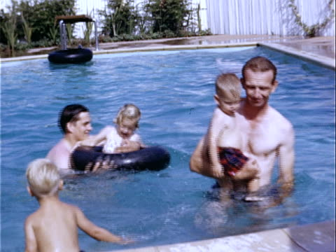1952 medium shot two fathers with young girl and boys swimming in backyard pool / beverly hills, california, usa  - rubber ring stock videos & royalty-free footage