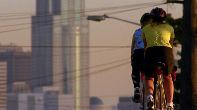 vídeos de stock, filmes e b-roll de medium shot two female cyclists riding away from cam on city hill w/buildings and power lines in background / seattle - capacete equipamento