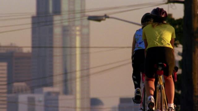 vídeos y material grabado en eventos de stock de medium shot two female cyclists riding away from cam on city hill w/buildings and power lines in background / seattle - casco herramientas profesionales