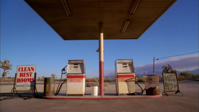 vídeos de stock e filmes b-roll de medium shot two gas pumps at gas station w/blue skies in background - gasolina