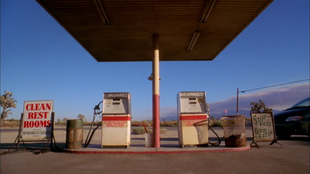 medium shot two gas pumps at gas station w/blue skies in background / van driving up / male driver getting out - petrol station stock videos & royalty-free footage