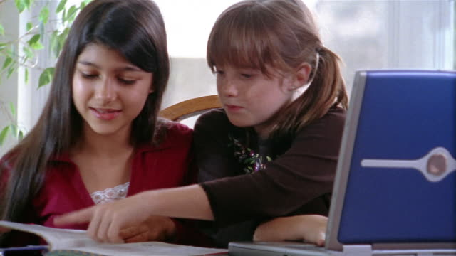 vídeos y material grabado en eventos de stock de medium shot two girls doing homework together - efecto zoom