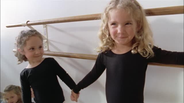vidéos et rushes de medium shot two girls holding hands and smiling at camera in dance studio / blonde girl putting her arm around brunette - barre de danse