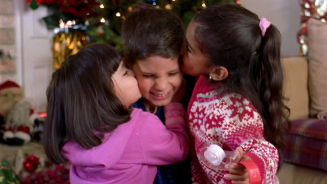 medium shot two girls kissing brother and making christmas decorations / smiling at cam / christmas tree in background - sister stock videos and b-roll footage