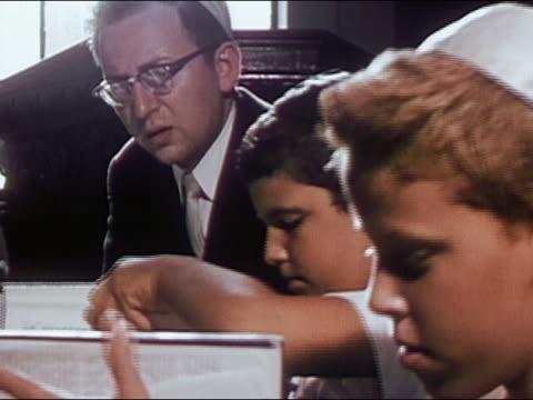 1955 medium shot two jewish boys studying the torah with a man / audio - torah stock videos and b-roll footage