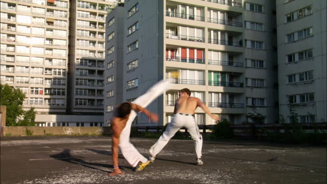 medium shot. two male capoeira dancers sparring on roof. - brazilian culture stock videos & royalty-free footage