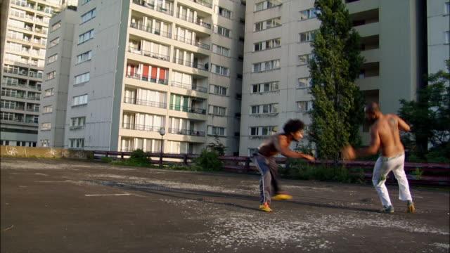 vídeos de stock, filmes e b-roll de medium shot. two male capoeira dancers sparring on roof. - posição de combate
