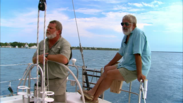 Medium shot Two mature men steering sailboat/ Harbor Island, Bahamas