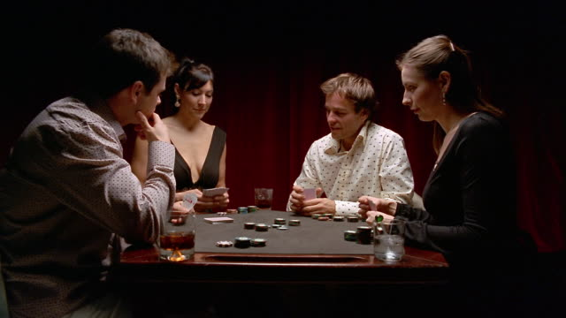 medium shot two men and two women playing cards (poker) at a table / women folding + one man winning the pot - playing card stock videos & royalty-free footage