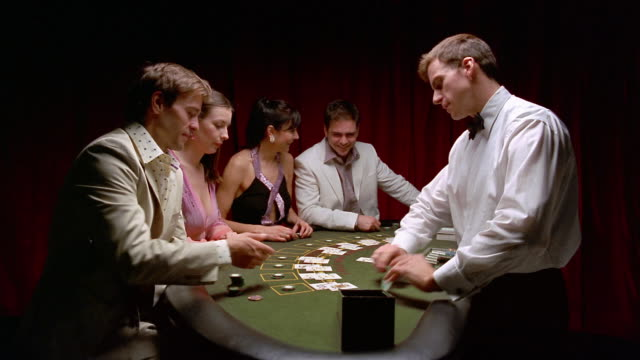 medium shot two men and two women sitting at blackjack table / dealer dealing cards / paying winners - blackjack video stock e b–roll