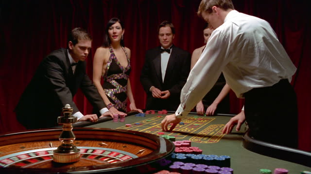 medium shot two men and two women standing at roulette table + placing bets / croupier spinning roulette wheel - roulette stock videos and b-roll footage