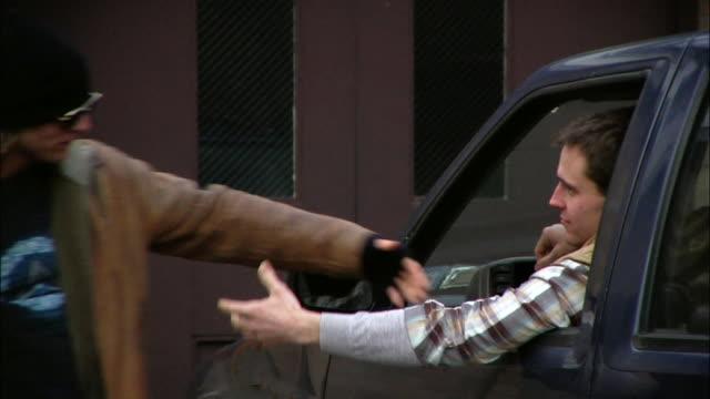 Medium shot Two men giving each other street handshakes near SUV / New York City, New York, USA