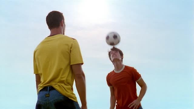 medium shot two men heading soccer ball back and forth / somerset west, south africa - 渡す点の映像素材/bロール