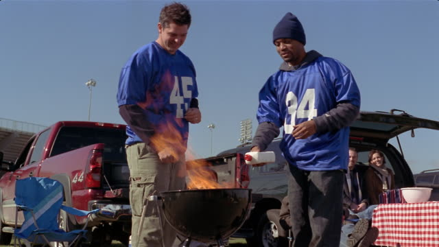 vídeos de stock, filmes e b-roll de medium shot two men igniting barbeque grill at tailgate party, high-fiving, then body slamming into one another/ connecticut - acendendo