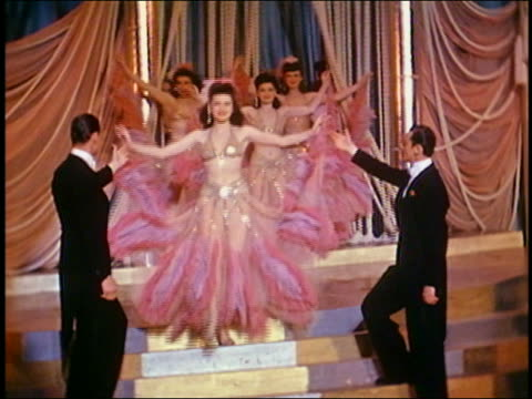 medium shot two men in tuxedos escorting female dancers walking onstage in costumes w/sequins and feathers - showgirl stock videos and b-roll footage