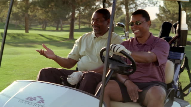 medium shot two men riding in golf cart and talking - golf cart stock videos & royalty-free footage