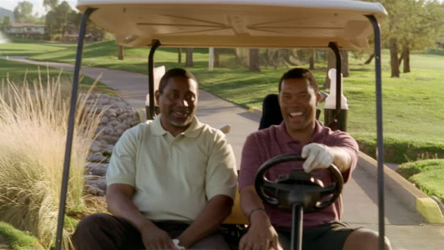 medium shot two men riding in golf cart and talking - golf cart stock videos and b-roll footage