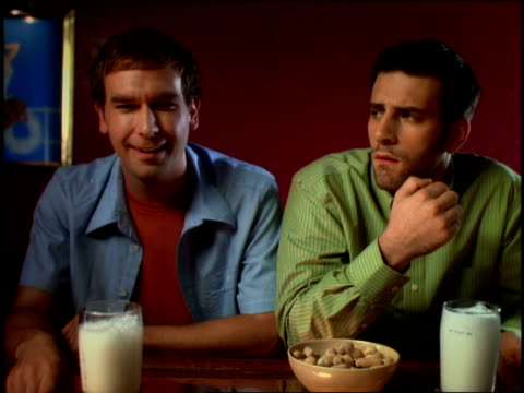 medium shot two men sitting at a bar talking and eating peanuts over foamy pints of beer / smiling - erdnuss stock-videos und b-roll-filmmaterial