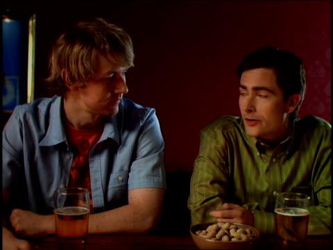 medium shot two men sitting at a bar talking and eating peanuts / smiling - 食品 ピーナッツ点の映像素材/bロール