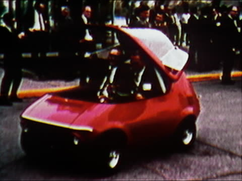 1970 medium shot two men sitting in tiny red prototype fuel-efficient car / man pulling roof down on car - small stock videos & royalty-free footage